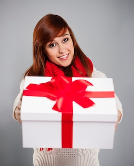 Brunette jeune femme donnant un cadeau de noël blanc avec ruban rouge