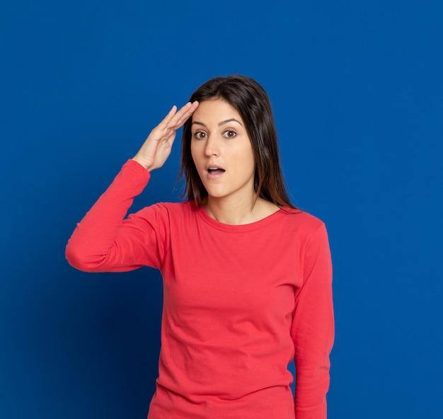 Brunette jeune femme gesticulant sur mur bleu