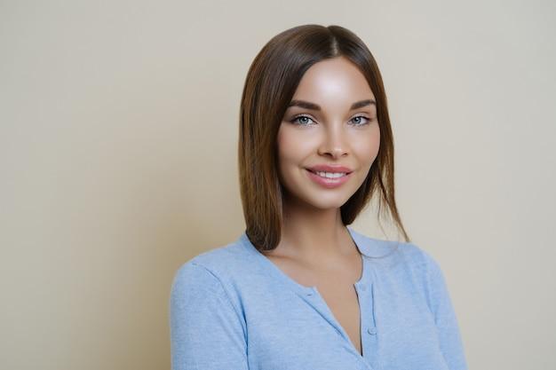Brunette jeune femme avec une peau de beauté saine, sourit doucement, montre des dents blanches parfaites