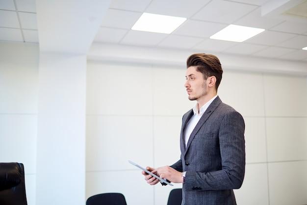 Brunette jeune homme d'affaires avec tablette au bureau