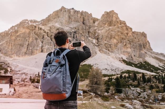 Brunette jeune homme avec grand sac à dos passer du temps en plein air sous un ciel gris profitant d'un paysage rocheux