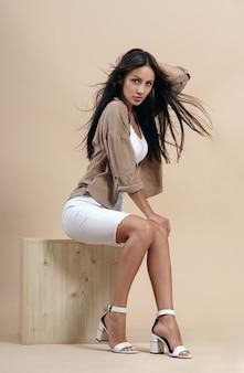 Brunette jolie femme portant des vêtements décontractés et assis sur un cube en bois sur beige