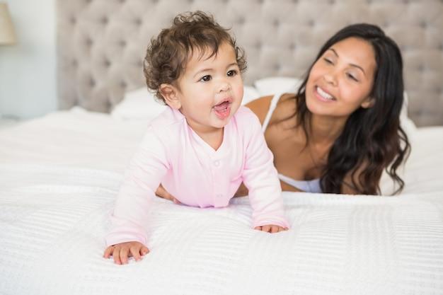 Brunette joue avec son bébé sur le lit