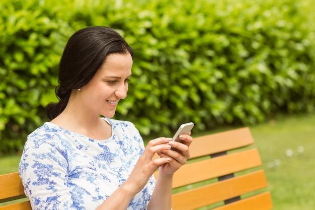Brunette joyeuse assis sur des textos de banc