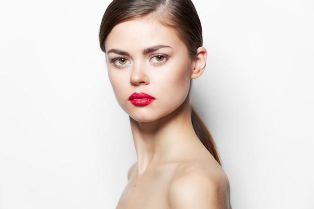 Brunette lèvres rouges épaules nues look attrayant maquillage lumineux