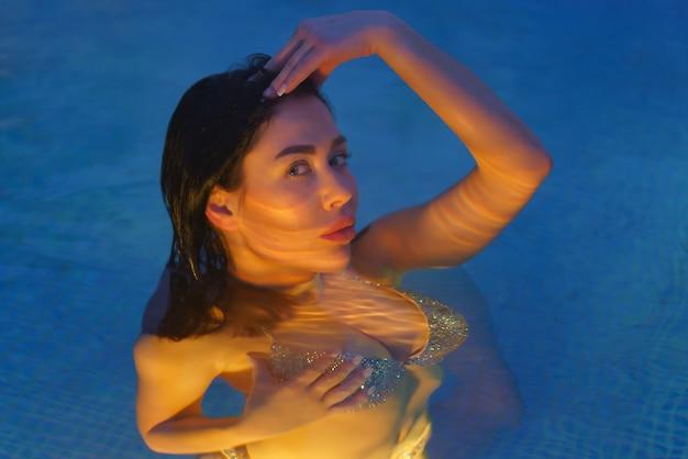 Brunette en maillot de bain détente dans l'eau géothermique dans la piscine du spa de balnéothérapie, stations thermales. corps de femme éclairé sous l'eau par des veilleuses dans la piscine. mise au point sélective douce sur les yeux du modèle.