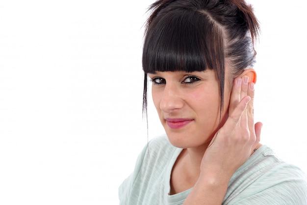Brunette avec un mal d'oreille sur le mur blanc