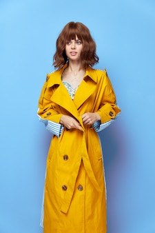 Brunette manteau jaune regarde sur le côté avec des vêtements élégants cheveux courts close up