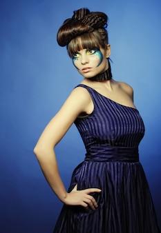 Brunette avec maquillage créatif en robe bleue