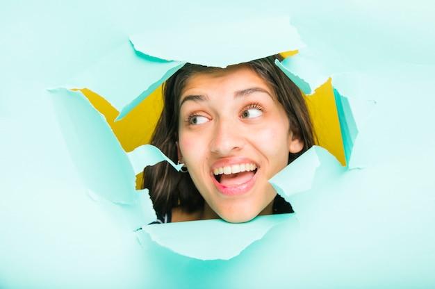 Brunette modèle posant à travers un trou de papier