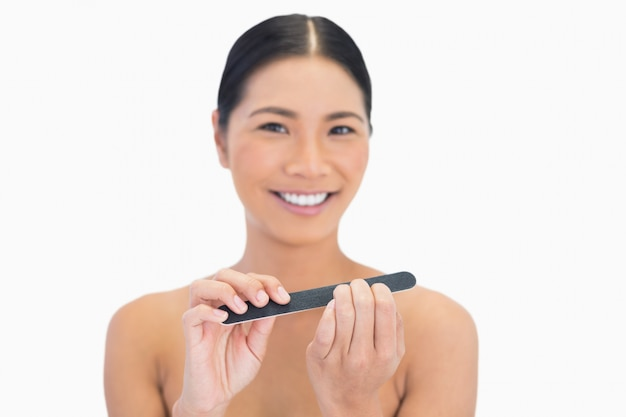 Brunette naturelle souriante utilisant une lime à ongles