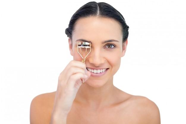Brunette naturelle souriante en utilisant un recourbe-cils