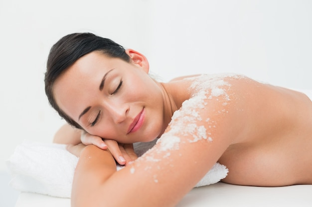 Brunette paisible allongé avec gommage au sel sur les épaules