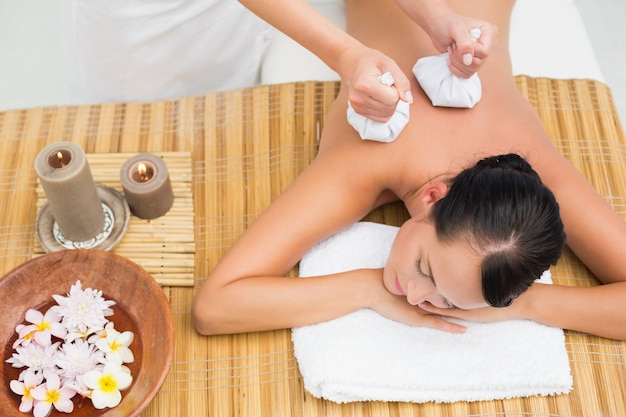 Brunette paisible bénéficiant d'un massage aux compresses aux herbes