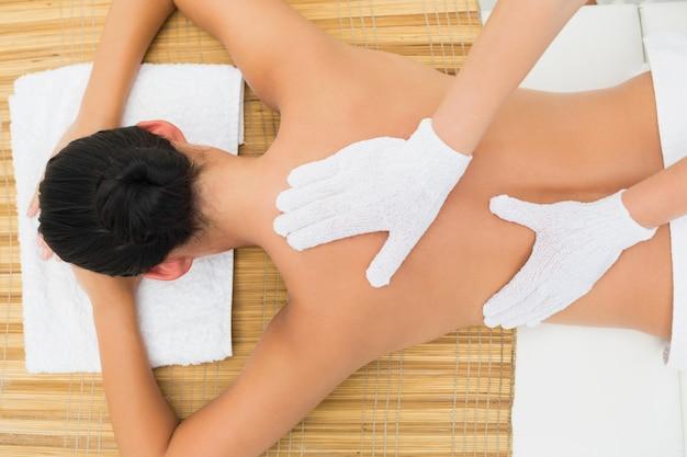 Brunette paisible bénéficiant d'un massage du dos exfoliant