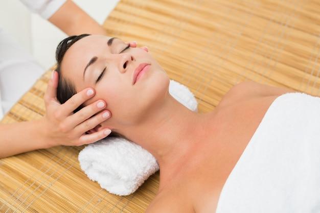 Brunette paisible bénéficiant d'un massage de la tête