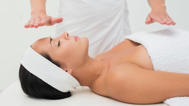Brunette paisible recevant une thérapie de reiki