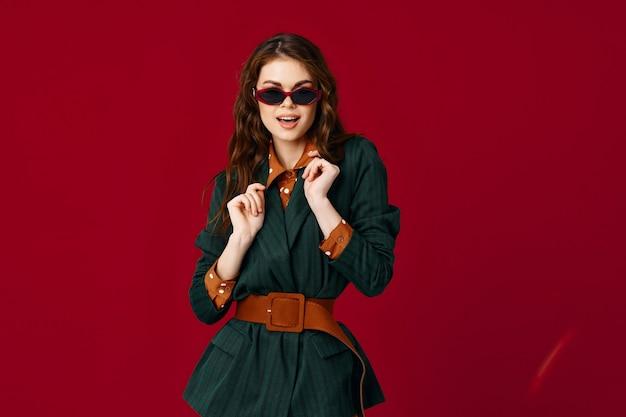 Brunette portant des lunettes de soleil en costume fashion style moderne fond rouge