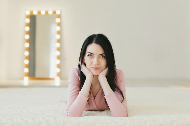 Brunette en pull rose est allongée sur le lit