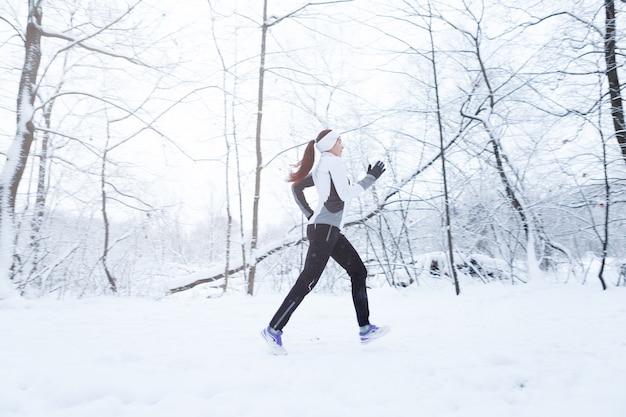 Brunette qui court dans le parc d'hiver