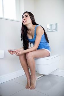 Brunette en regardant son test enceinte dans les toilettes