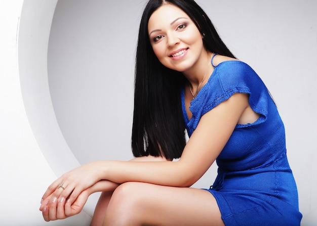 Brunette en robe bleue assise en cercle
