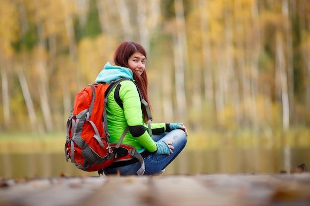 Brunette avec sac à dos assis sur le pont au bord du lac