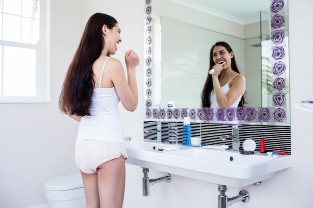 Brunette se brosser les dents dans la salle de bain