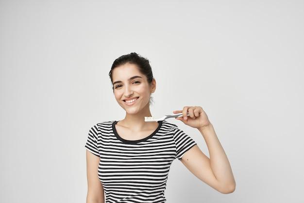 Brunette se brosser les dents avec un fond clair de brosse à dents
