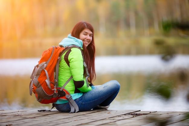 Brunette souriante assise avec sac à dos sur le pont