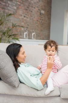 Brunette souriante jouant avec son bébé sur le canapé