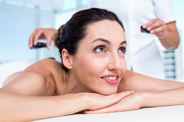 Brunette souriante obtenir massage aux pierres chaudes