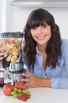 Brunette souriante avec presse-agrumes pleine de fruits