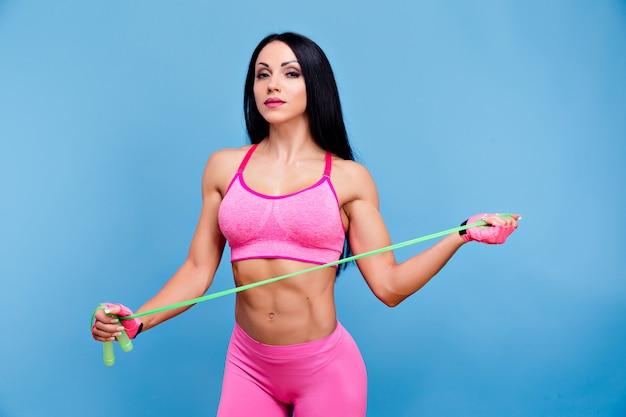 Brunette sportive dans le sportswear rose avec une corde à sauter