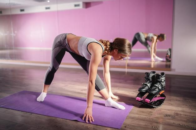 Brunette sportive saine qui s'étend de jambes en se tenant debout sur le tapis dans la salle de gym. à côté de ses chaussures kangoo jumps