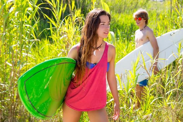 Brunette surfeuse marchant dans la jungle