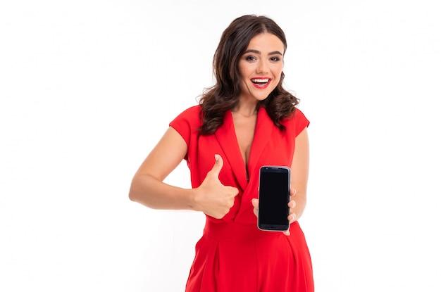 Brunette tenant un téléphone dans ses mains sur une surface isolée blanche, avec un large sourire montre un geste de super