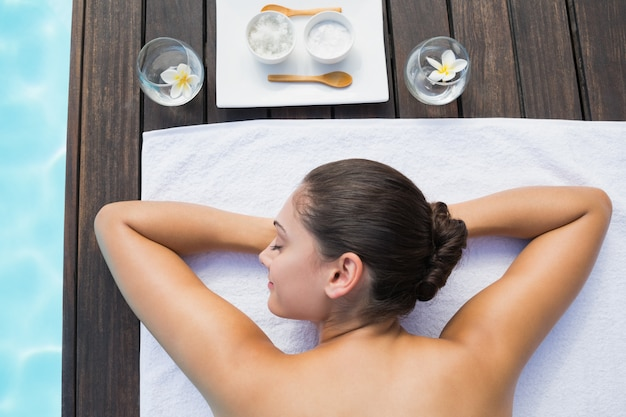 Brunette tranquille allongé sur une serviette au bord de la piscine avec des traitements de beauté