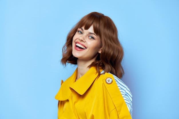 Brunette vue latérale des vêtements à la mode manteau jaune lèvres rouges