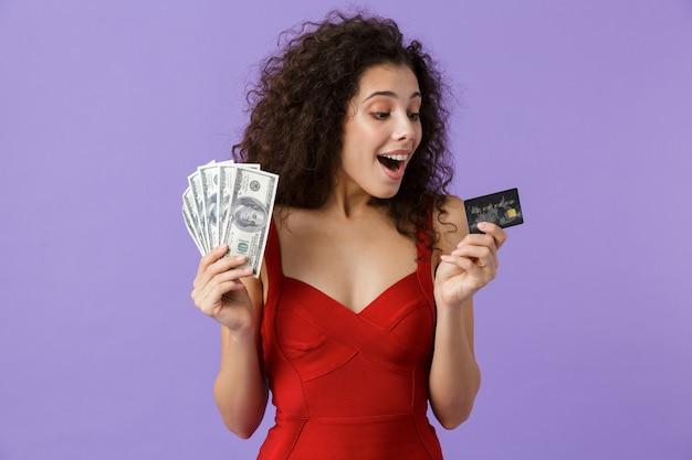 Brunette woman wearing red dress holding fan d'argent et carte de crédit, debout isolé sur mur violet