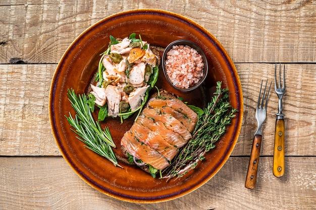 Bruschetta au saumon fumé chaud et froid, roquette, câpres sur une assiette rustique aux herbes. fond en bois. vue de dessus.