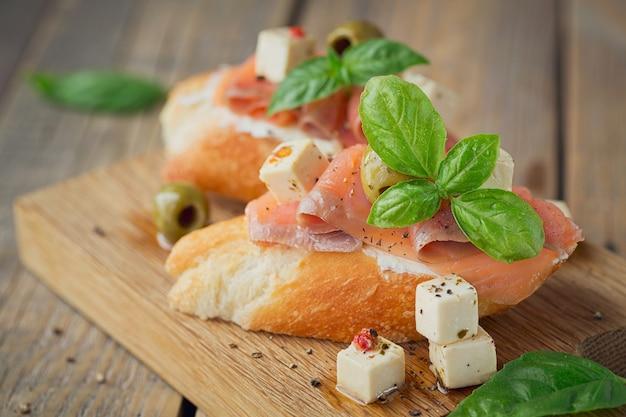 Bruschetta au saumon fumé, fromage à la crème, olives et roquette