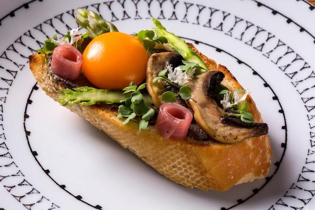 Bruschetta aux champignons frits et jaune d'oeuf sur une assiette