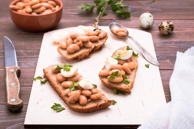 Bruschetta aux haricots à la sauce tomate, oeufs de caille et persil