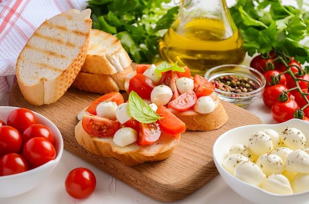 Bruschetta aux tomates cerises et mozzarella sur une planche à découper en bois.
