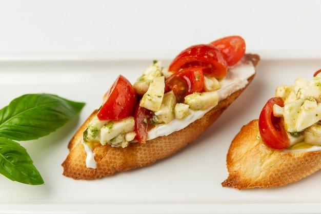 Bruschetta aux tomates et fromage sur une assiette. entrée appétissante. fond blanc. espace pour le texte.