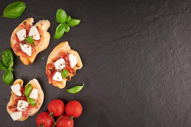 Bruschetta aux tomates, fromage mozzarella et basilic sur une planche à découper. apéritif ou collation italienne traditionnelle, antipasti. bruschetta de salade caprese. vue de dessus avec espace de copie. mise à plat.