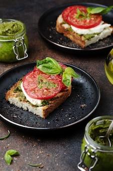Bruschetta aux tomates pesto maison et mozzarella sur l'assiette pesto frais dans des bocaux en verre