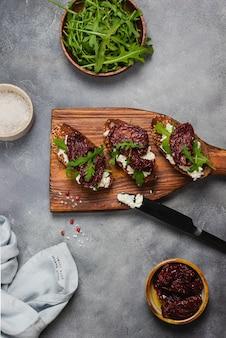 Bruschetta aux tomates séchées avec fromage cottage, ail, roquette, pain de grains entiers et huile d'olive servie sur un fond de pierre grise avec une serviette en lin bleu et un couteau noir. flatlay.