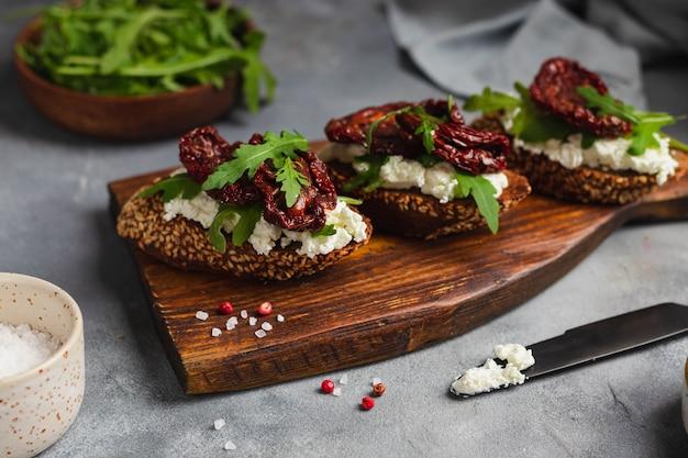 Bruschetta aux tomates séchées avec fromage cottage, ail, roquette, pain de grains entiers et huile d'olive